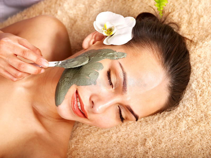 Young woman with clay facial mask. Beautiful young woman with clay facial mask stock photo