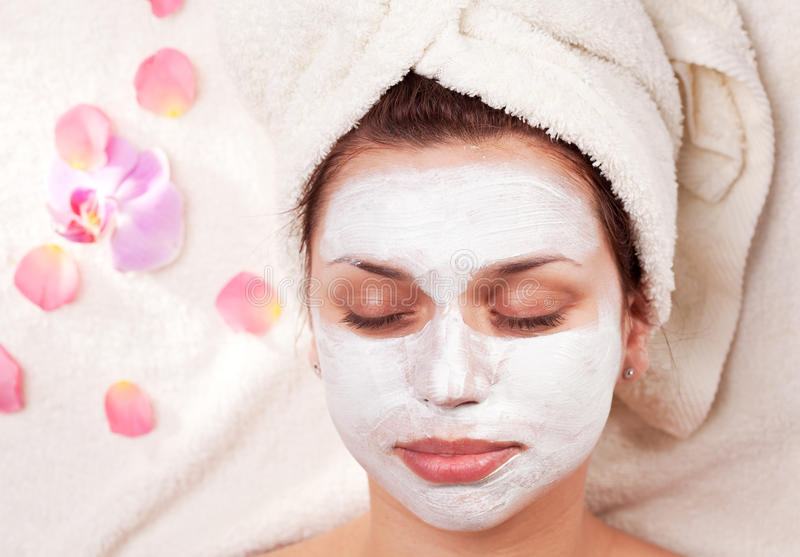 Young woman with clay facial mask. Young woman with clay facial mask in beauty salon royalty free stock image