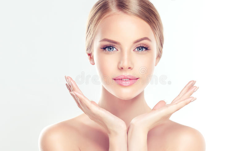 Young Woman with clean, fresh, skin. Portrait of beautiful Young Woman with clean, fresh, skin touching her face. Facial treatment. Cosmetology, beauty and spa