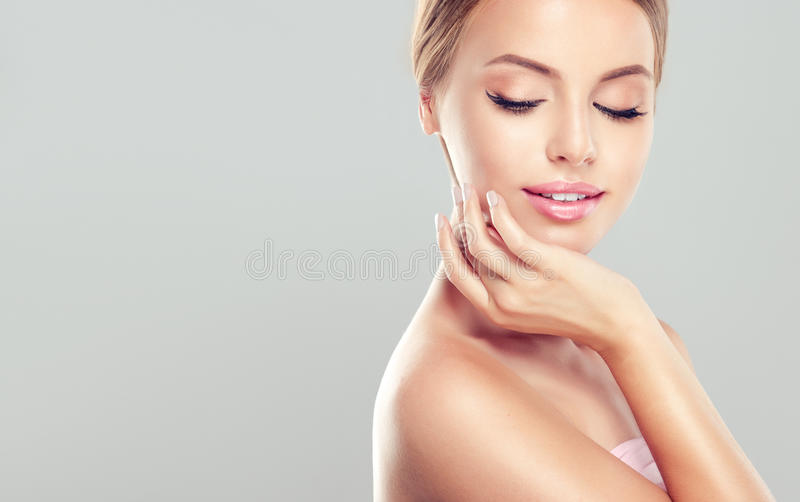 Young Woman with clean, fresh, skin. Portrait of beautiful Young Woman with clean, fresh, skin touching her face. Facial treatment. Cosmetology, beauty and spa stock image
