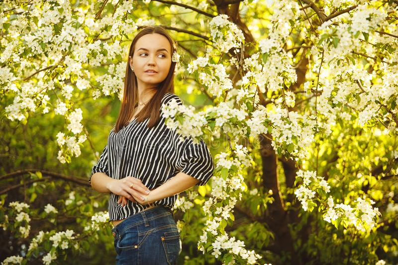 Young woman with clean skin near a blooming apple tree. portrait of girl in spring park. Spring shot of cute person royalty free stock images