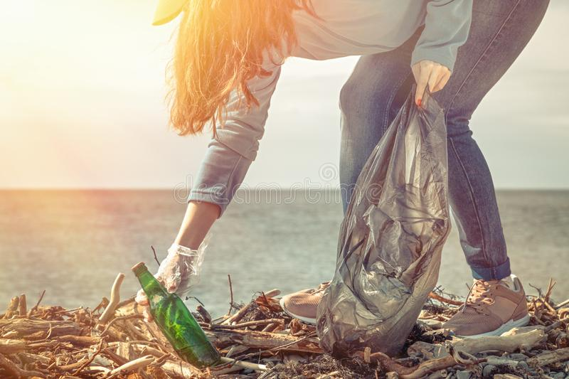 A young woman on a clean-up of the coastal area, collecting garbage. Sea and sky in the background. Earth day and ecology. Light stock image
