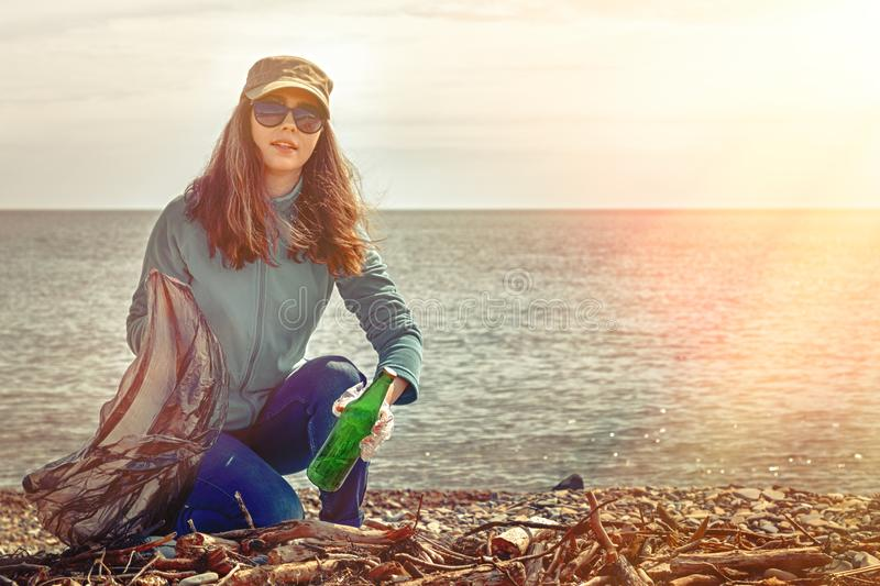 A young woman on a clean-up coastal area. Sea and sky in the background. Earth day and ecology. Copy space. Light.  stock image