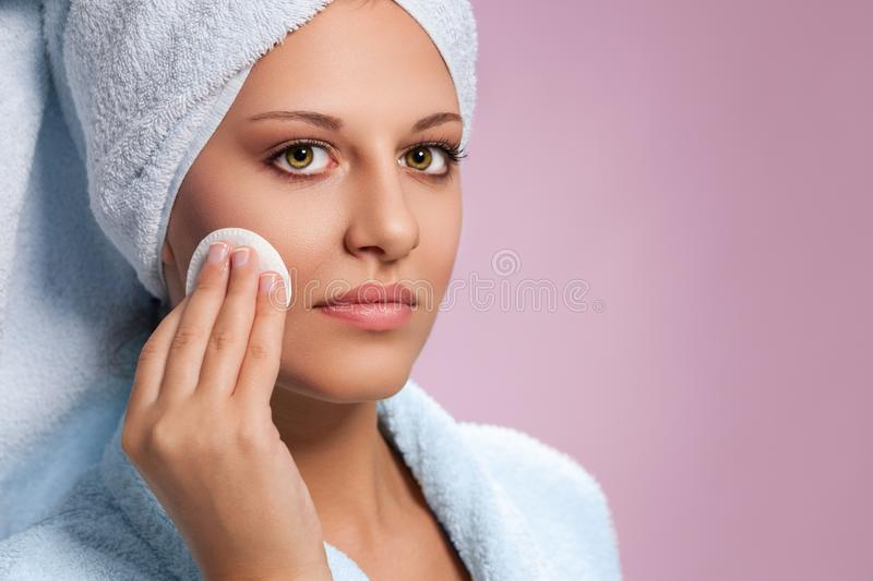 Young woman cleaning face with cotton pad stock image