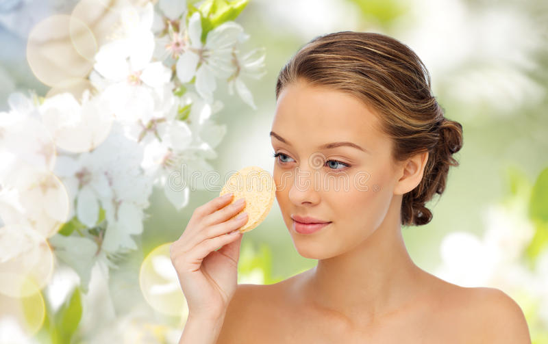 Young woman cleaning face with exfoliating sponge stock photography