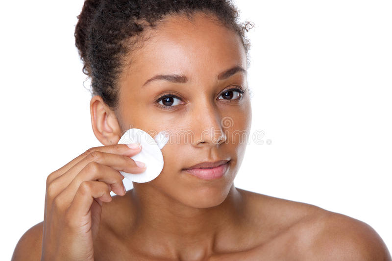 Young woman cleaning face with make up removal sponge royalty free stock photography