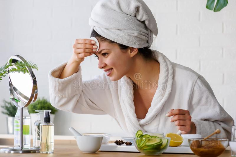 Young woman cleaning face with natural cosmetics. Clean fresh skin care. stock image