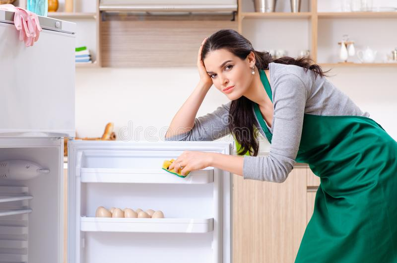 The young woman cleaning fridge in hygiene concept. Young woman cleaning fridge in hygiene concept stock photography