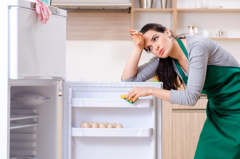 The young woman cleaning fridge in hygiene concept. Young woman cleaning fridge in hygiene concept stock image
