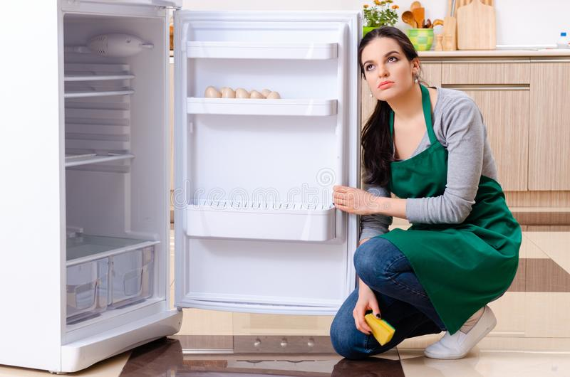 The young woman cleaning fridge in hygiene concept. Young woman cleaning fridge in hygiene concept royalty free stock image