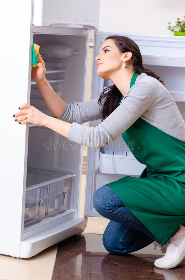 The young woman cleaning fridge in hygiene concept. Young woman cleaning fridge in hygiene concept royalty free stock photography