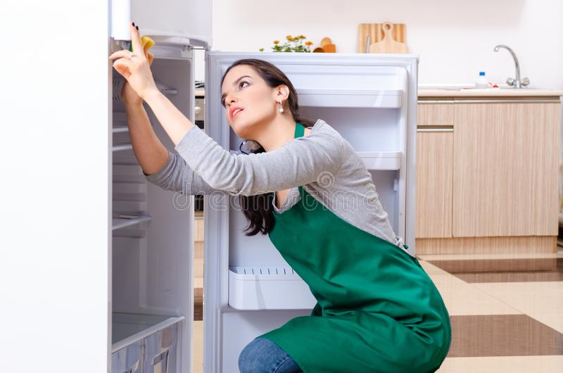 Young woman cleaning fridge in hygiene concept. The young woman cleaning fridge in hygiene concept stock photo
