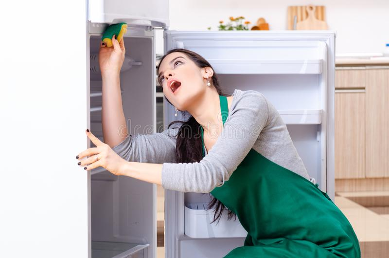 Young woman cleaning fridge in hygiene concept. The young woman cleaning fridge in hygiene concept stock photos