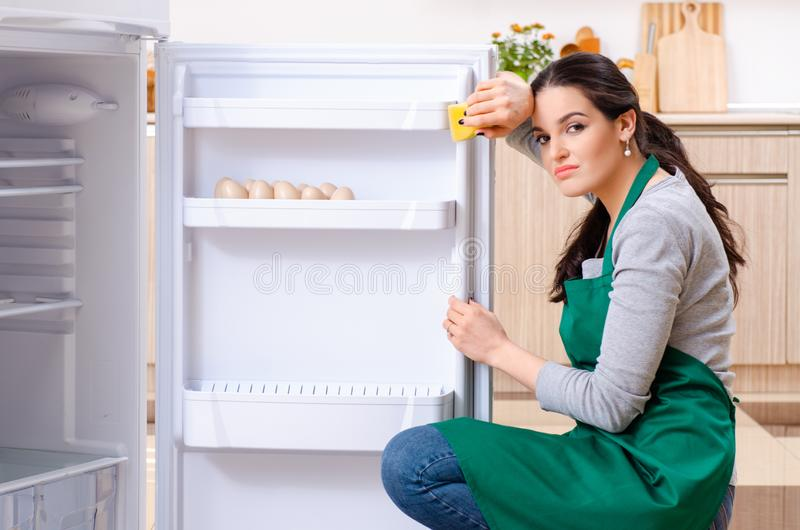 Young woman cleaning fridge in hygiene concept. The young woman cleaning fridge in hygiene concept royalty free stock image