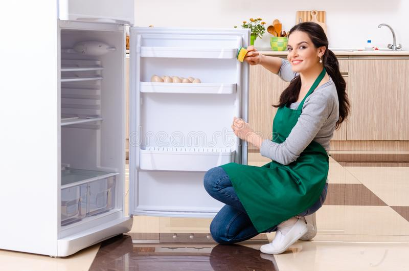 Young woman cleaning fridge in hygiene concept. The young woman cleaning fridge in hygiene concept royalty free stock photos