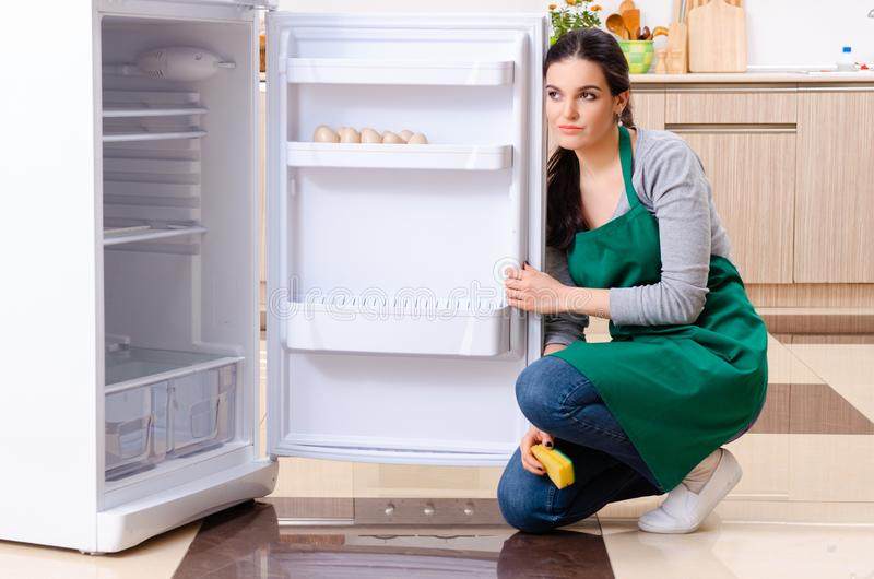 Young woman cleaning fridge in hygiene concept. The young woman cleaning fridge in hygiene concept royalty free stock images