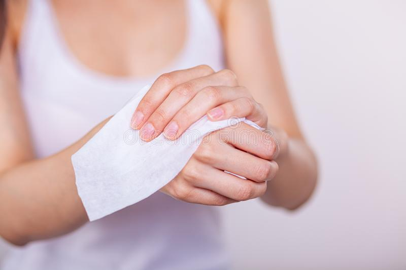 Women cleaning hands with wet wipes. Young woman cleaning hands with wet wipes, white royalty free stock photo