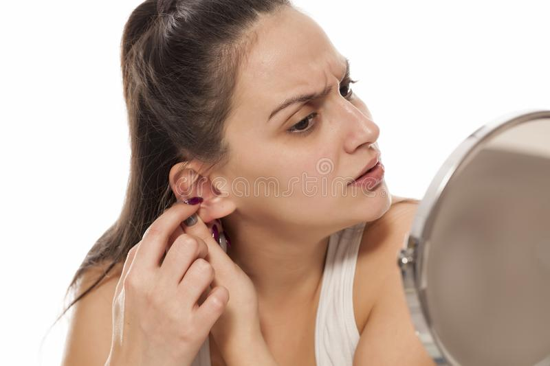 Woman cleaning her ears stock images
