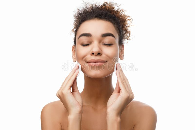 Young woman cleaning her face with cotton pads stock photos