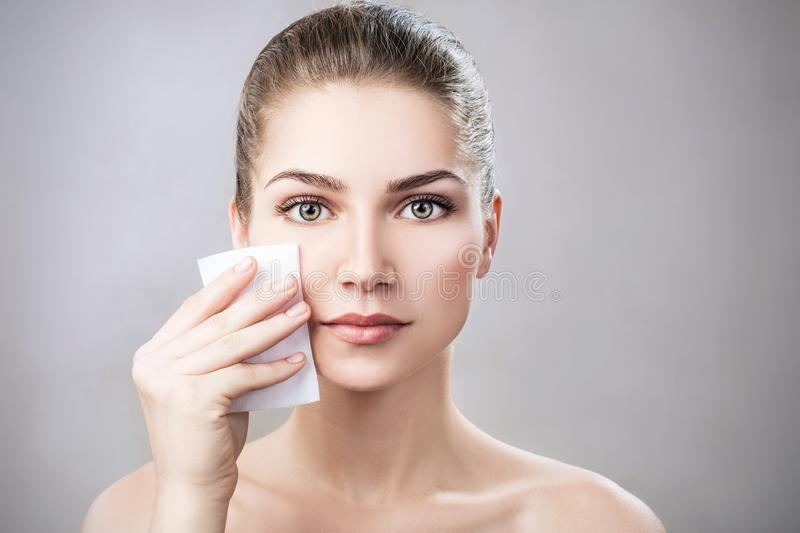 Young woman cleaning her face by napkins. Skincare concept. Maku-up removal napkins stock image