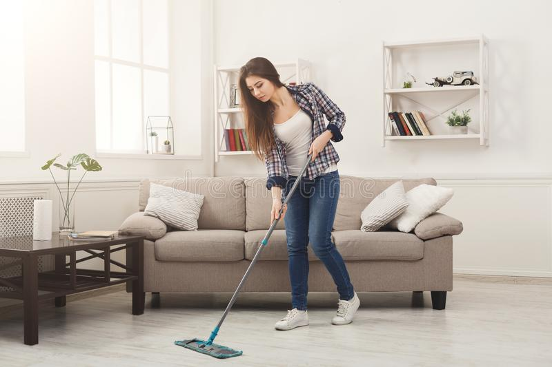 Young woman cleaning house with mop. Young woman cleaning house, washing floor with mop, copy space stock photo