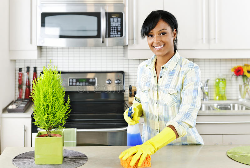 Young woman cleaning kitchen royalty free stock photo