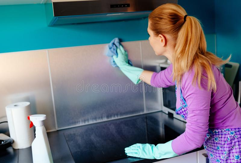 Young woman cleaning kitchen cabinets royalty free stock photos