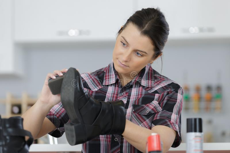 Young woman cleaning shoes in kitchen royalty free stock photo