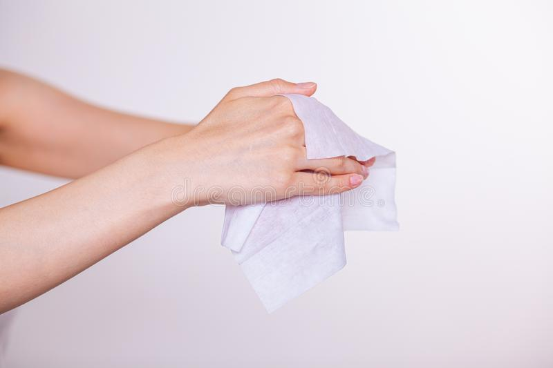 Two hands cleaning with wet wipes. Young woman cleaning skin of two hands with wet wipes, white stock image
