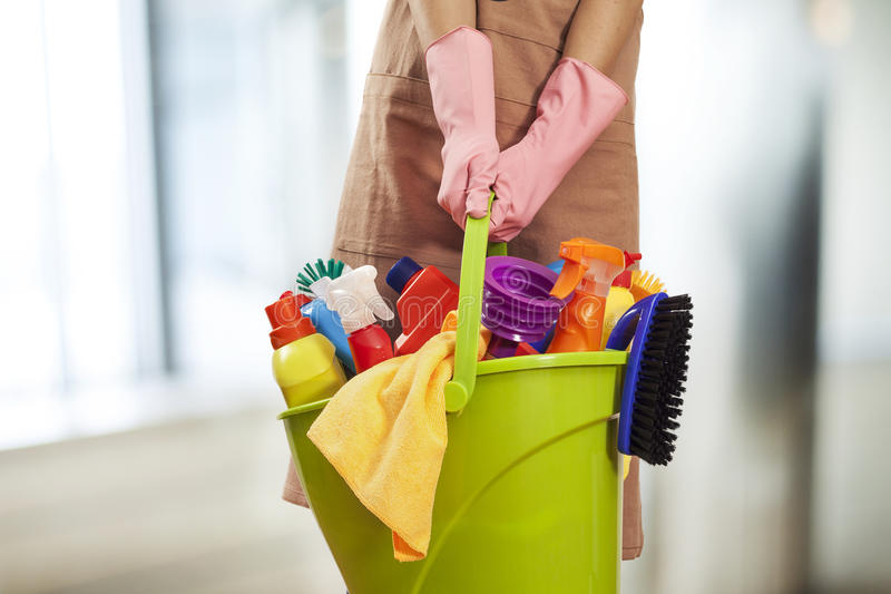 Young woman cleaning supplies in home stock photography
