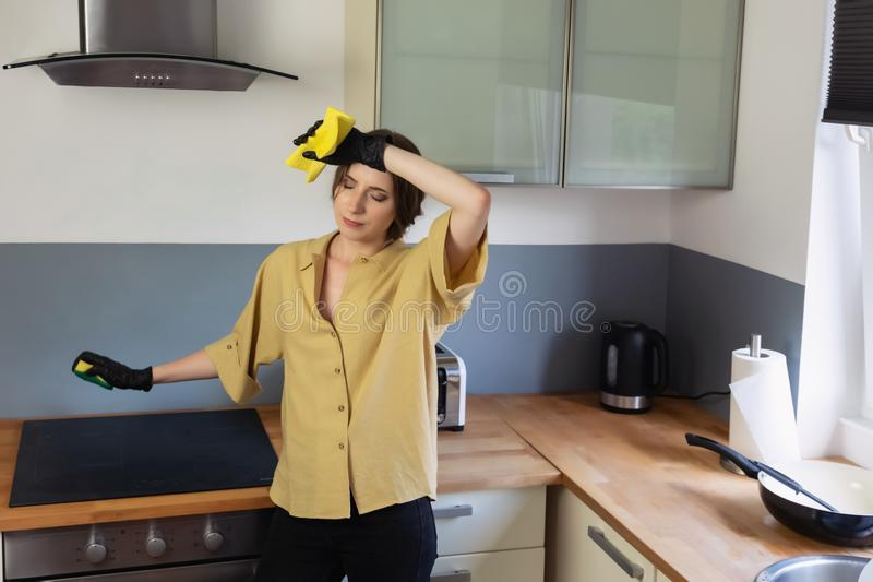 A young woman cleans up in the kitchen, washing dishes. stock images