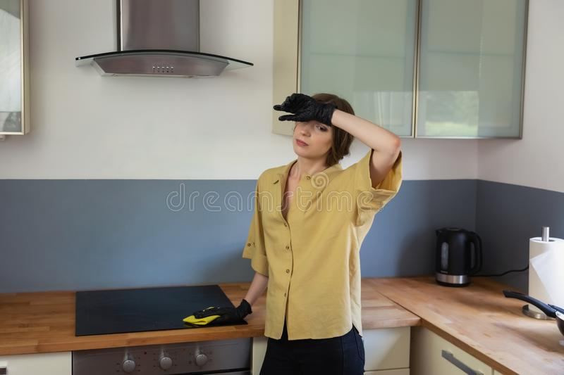 A young woman cleans up in the kitchen, washing dishes. royalty free stock photo
