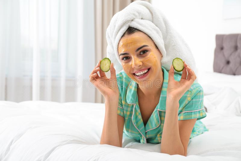 Young woman with cleansing mask on her face holding cucumber slices. In bedroom royalty free stock photo