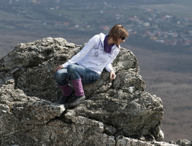 Young woman on cliff edge. Looks down royalty free stock photos