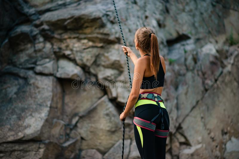 Young Woman Climber Belayer Holding the Rope near the Rock in the Mountains. Adventure and Extreme Sport Concept stock images