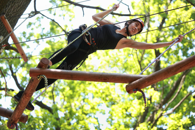 Young woman climbing in adventure rope park royalty free stock photography
