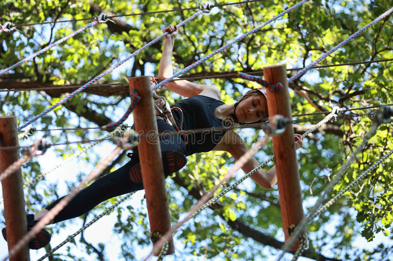 Young woman climbing in adventure rope park stock photography