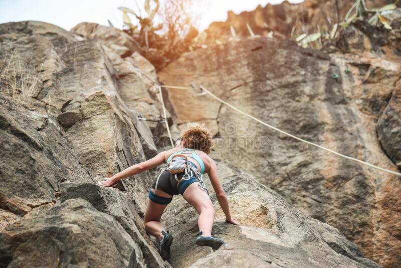 Young woman climbing a rock wall in a canyon - Strong climber training outdoor - Travel, adrenaline and extreme dangerous sport. Concept - Focus on her body stock photos