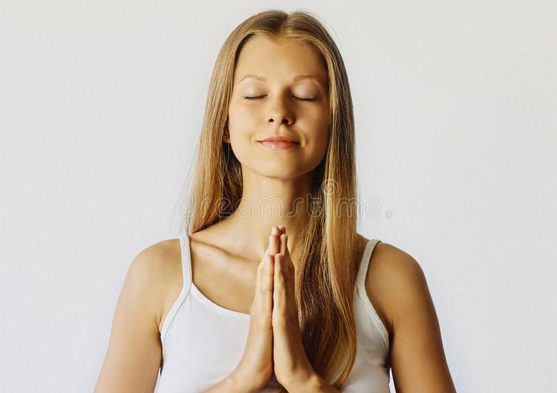 Young woman with closed eyes and hands in praying gesture. Meditation, balance and peace of mind concept. Isolated over white stock image