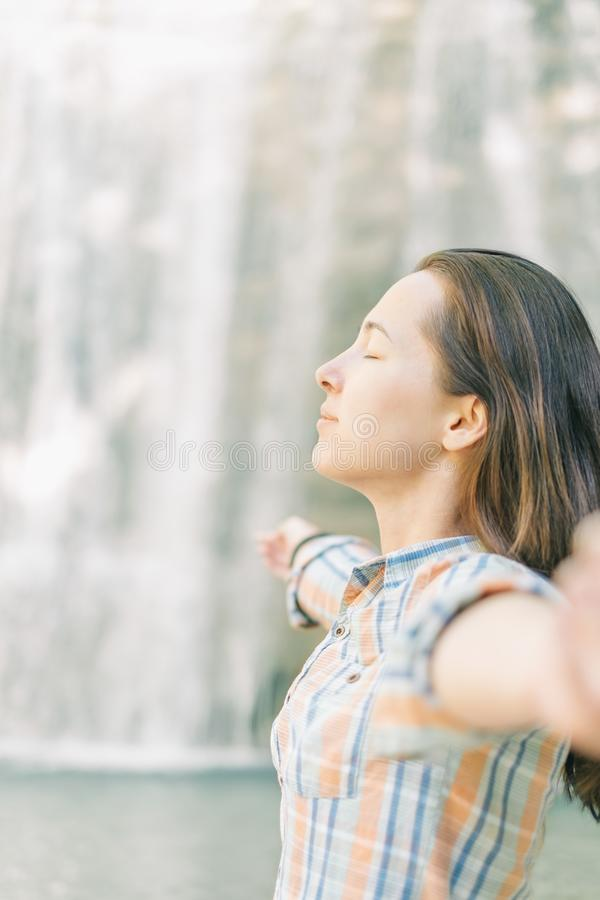 Young woman relaxing on background of waterfall. Young woman with closed eyes meditating with raised arms on background of waterfall outdoor, side view royalty free stock photography