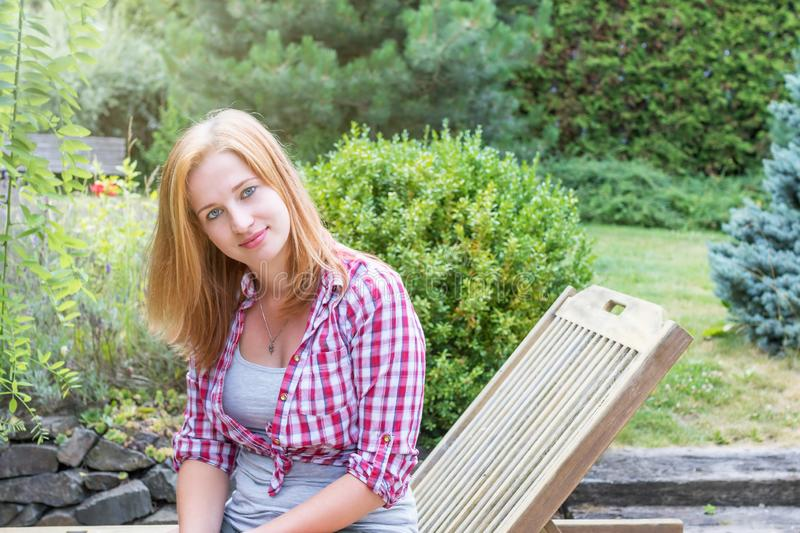 Young woman clothed in checkered shirt is posing. Smiling attractive young woman clothed in checkered shirt is posing in the garden royalty free stock images