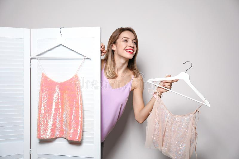Young woman with clothes on hangers behind folding screen against light background. royalty free stock photography