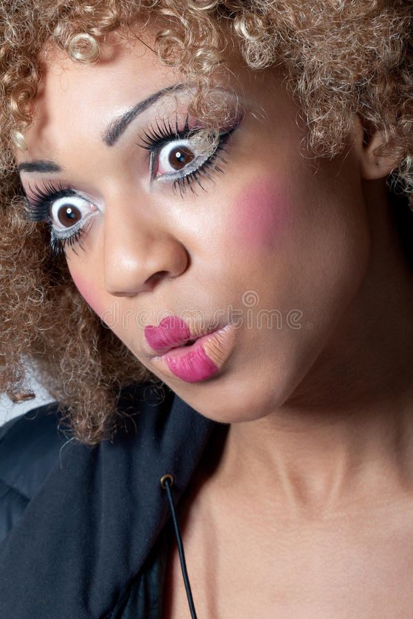 Young woman with clown make-up looking surprised