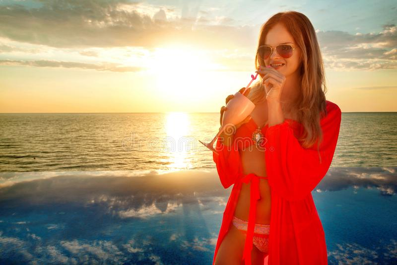 Young woman with coctail in summer dress standing on a pool and sea background . Sunset stock photos