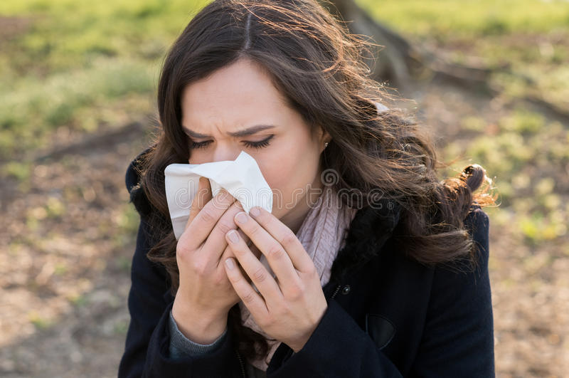 Young woman with cold. Portrait of young woman blowing her nose outdoor royalty free stock image