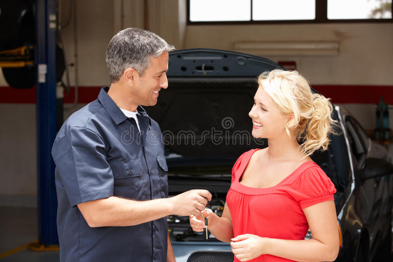 Young woman collecting car from repair shop royalty free stock photos