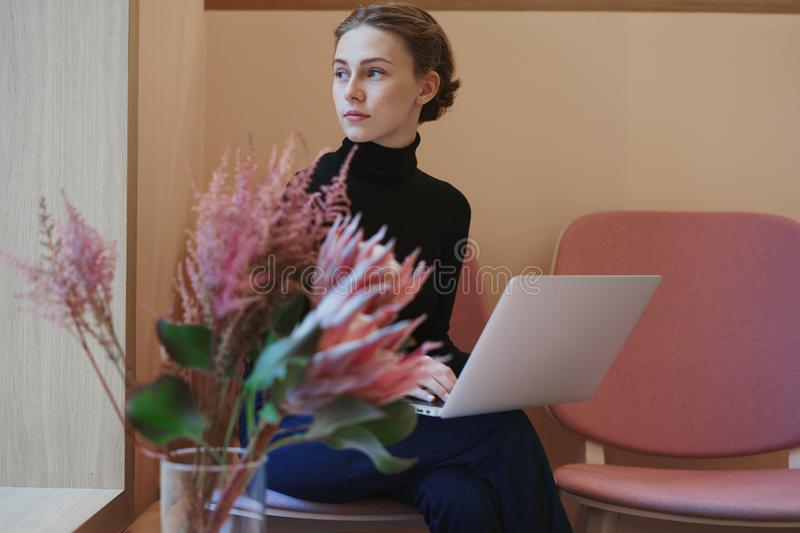 Young woman or college student working and writing using laptop on knees. Sitting in cafe near window, romantic mood, warm color. stock images