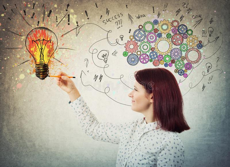 Draw idea. Young woman with colorful gear brain above head, positive emotion, drawing a genius idea as arrows and curves going to a color splash light bulb stock photography