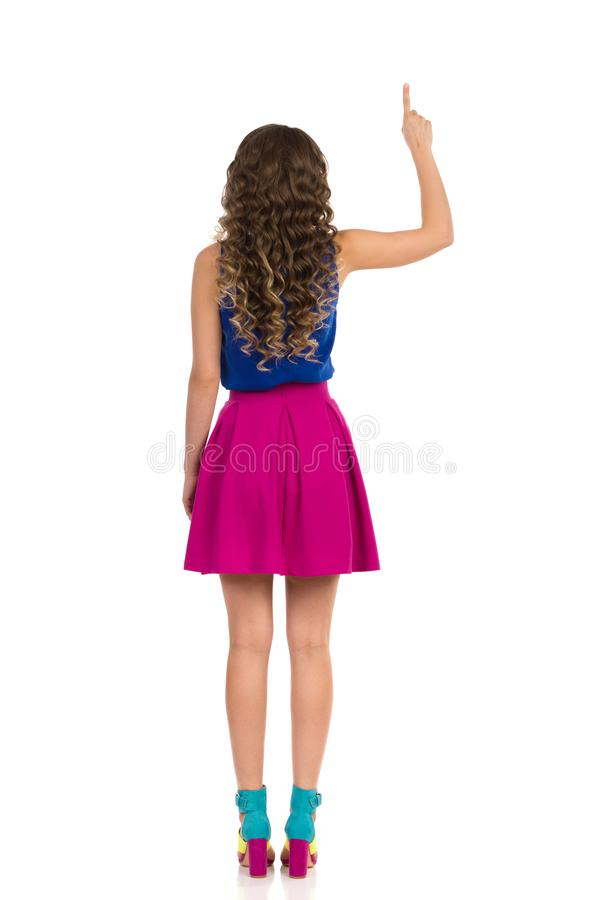 Young Woman In Colorful High Heels, Pink Mini Skirt And Blue Top Is Pointing Up, Rear View. Beautiful young woman in colorful high heels, pink mini skirt and royalty free stock images