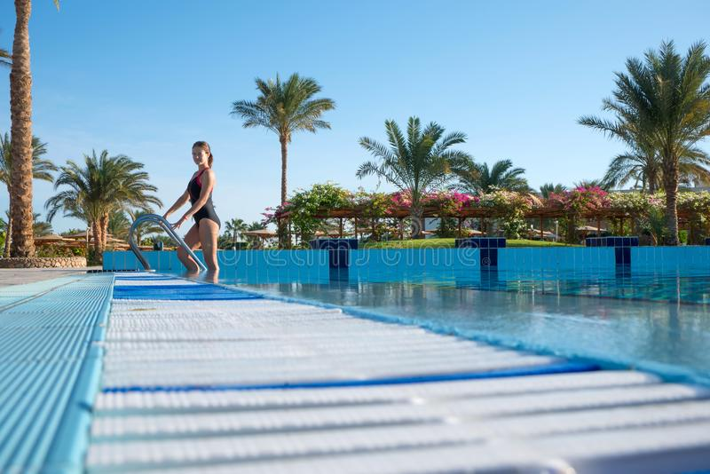 Young woman comes out of the sports pool in a beautiful piece-work swimsuit. Active rest of modern people at the resort. royalty free stock photography